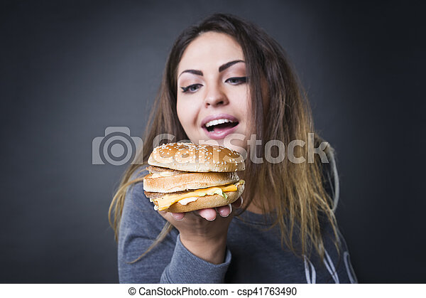 Happy beautiful young plus size model posing with hamburger on a gray studio background, xxl woman eating burger - csp41763490
