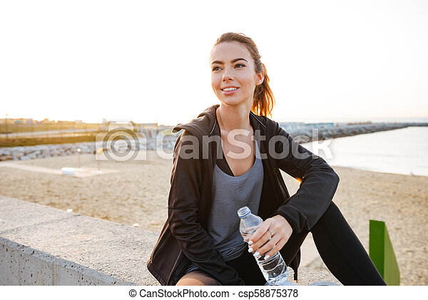 Happy beautiful young sports woman drinking water - csp58875378