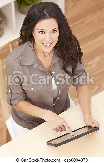 Happy Beautiful Young Woman Using Tablet Computer at Home - csp6094970