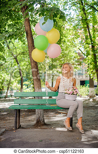 Happy and smiling birthday girl with a beautiful and soft bouquet of flowers and colorful balloons on the bench