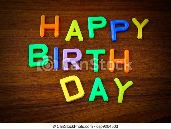 Happy Birthday in colorful toy letters on wood background - csp9204503