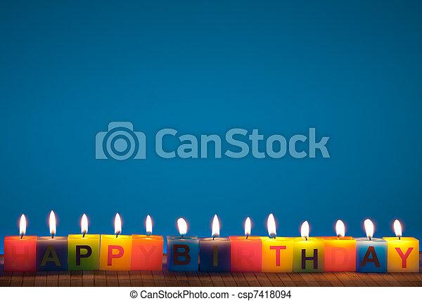 Happy birthday lit candles on blue - csp7418094