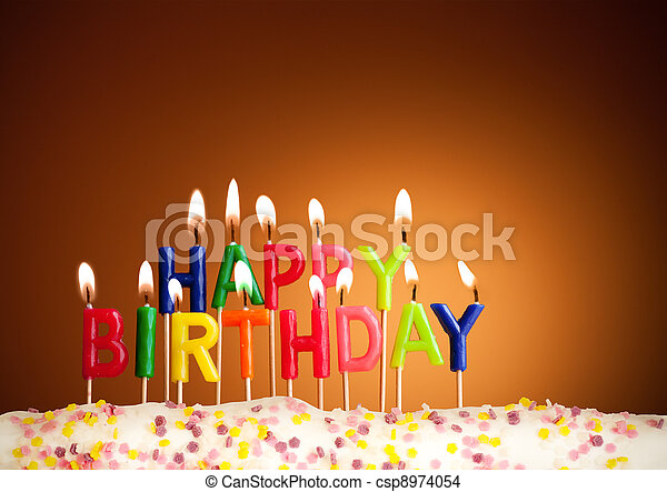 Happy birthday lit candles on brown background - csp8974054