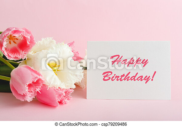 Happy Birthday text on gift card in flower bouquet. Beautiful bouquet of fresh flowers tulips with greeting card Happy Birthday on pink background. - csp79209486