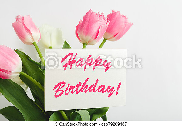 Happy Birthday text on gift card in flower bouquet. Beautiful bouquet of fresh flowers tulips with greeting card Happy Birthday on white background. - csp79209487