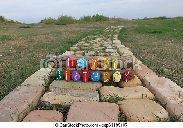 Happy Birthday text with colored stones on wood over a bricks road - csp61185197