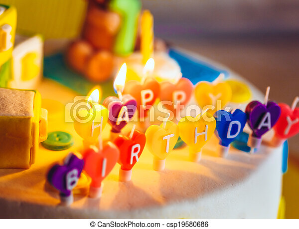 Happy birthday written in lit candles on colorful background - csp19580686