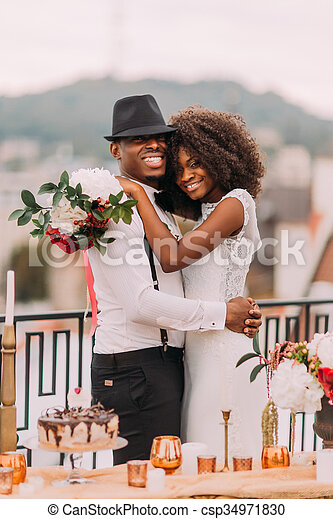 Happy black bride and stylish groom posing for camera on the terrace with cityscape on foreground - csp34971830