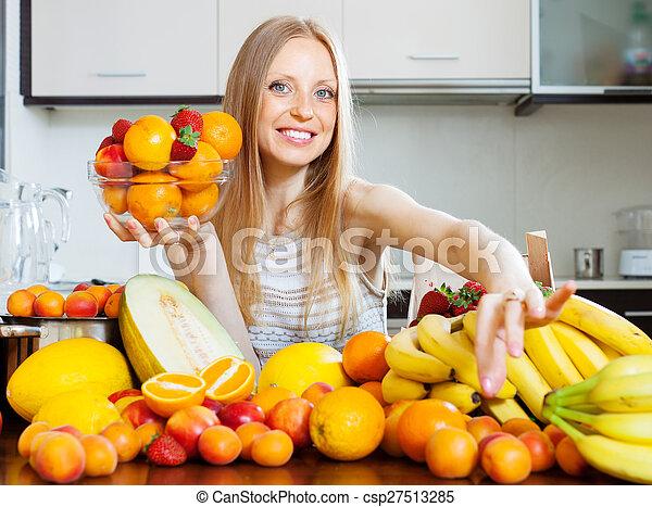Happy blonde woman choosing fruits - csp27513285