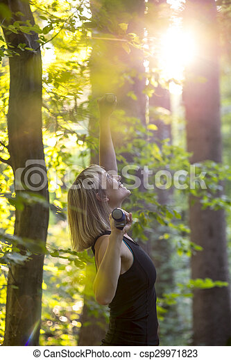 Happy blonde young woman doing pilates exercise in a forest at sunrise with dumbells - csp29971823