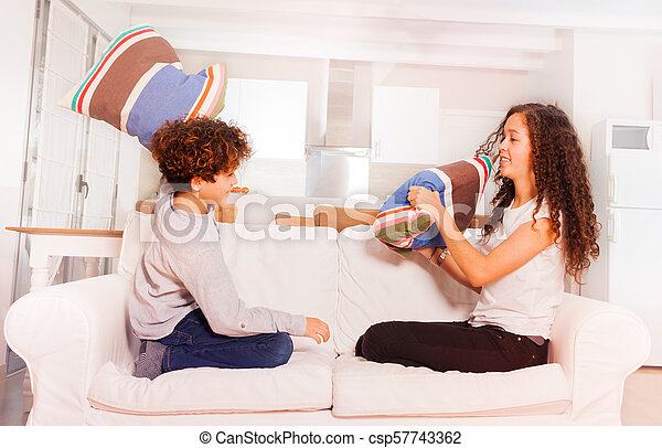 Happy boy and girl fighting with pillows at home - csp57743362