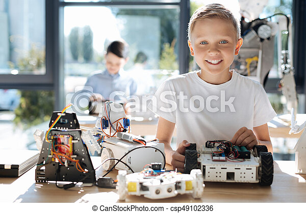 Happy boy posing with his robot models