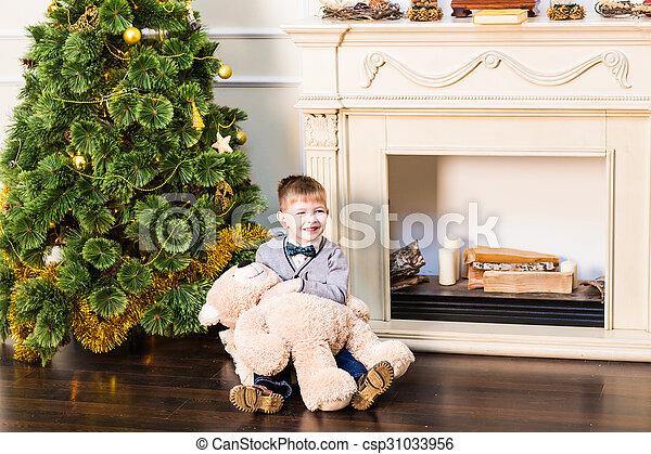 Happy boy with a teddy bear. Christmas tree. New Year - csp31033956