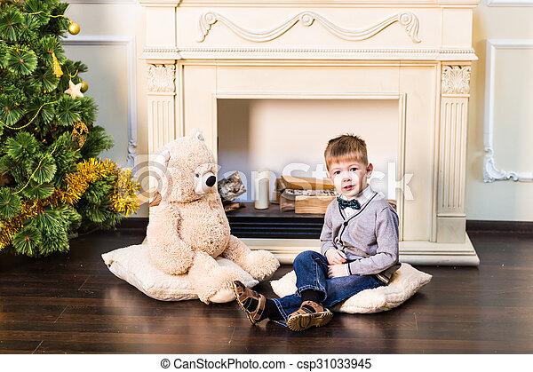 Happy boy with a teddy bear. Christmas tree. New Year - csp31033945