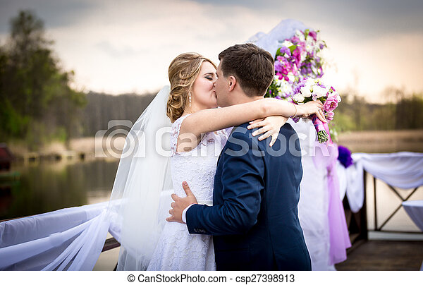 happy bride and groom kissing on sunset at river - csp27398913