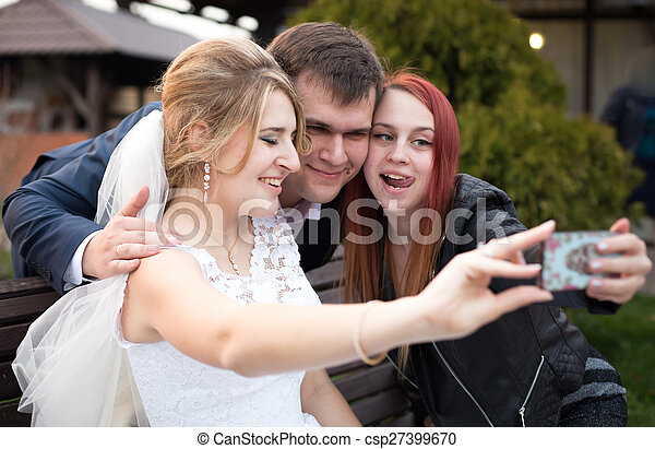 happy bride and groom making selfie with guest on wedding day - csp27399670