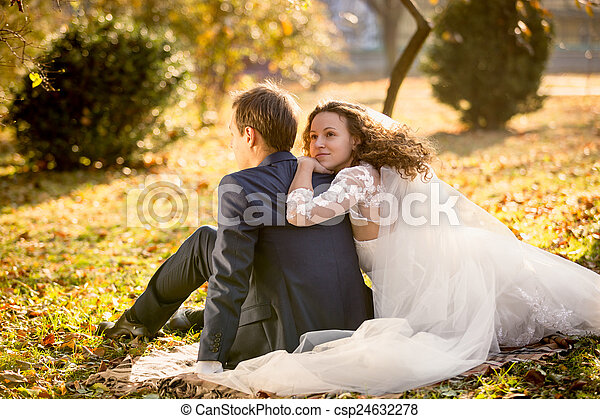 happy bride hugging groom sitting on yellow leaves at park - csp24632278
