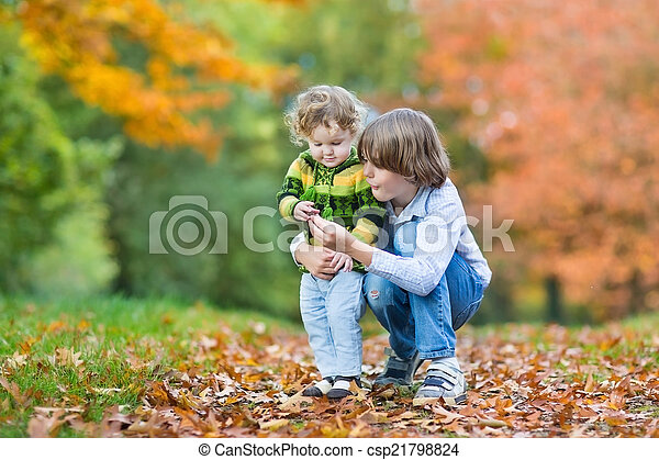 Happy brother and toddler sister playing together in a colorful  - csp21798824