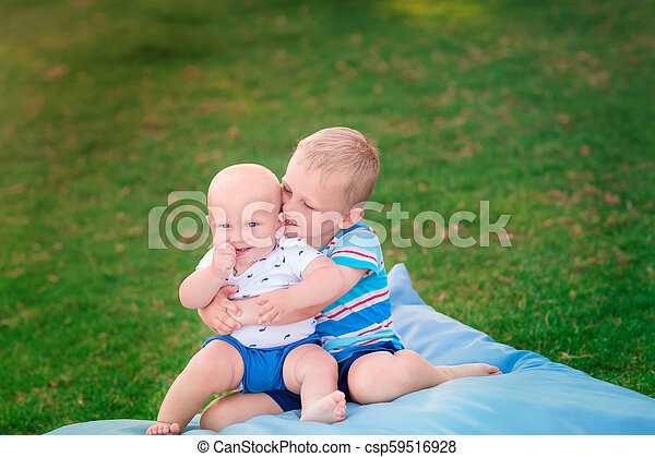 Happy brothers playing on the grass - csp59516928