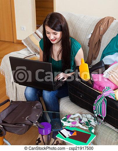 Happy brunette woman choosing resort online - csp21917500