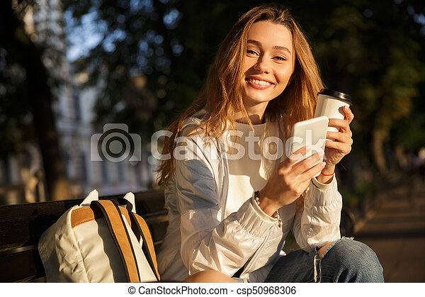 93db4b127a Happy brunette woman in autumn clothes sitting in park and looking ...