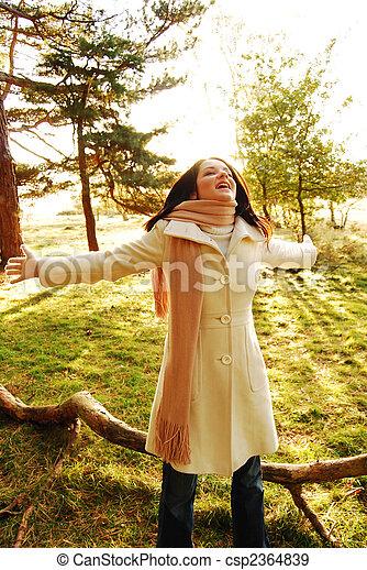 Happy brunette woman in autumn scene - csp2364839