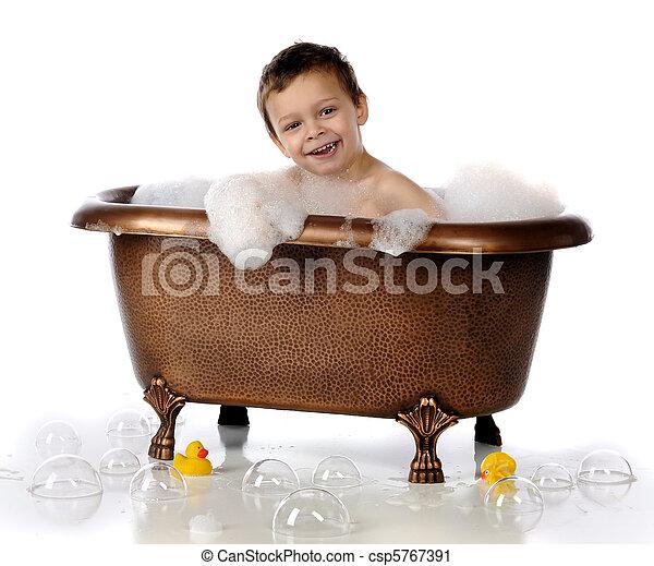 Happy bubble bath. A happy preschooler playing in a copper, claw ...