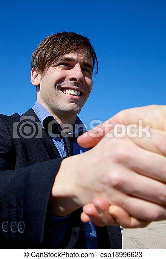 Happy business man shaking hand - csp18996623