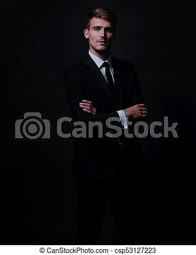 d6cfaeb2f6 Happy business man wearing black suit standing and folding arms ...