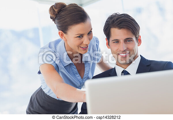 Happy business people looking together at the laptop  - csp14328212
