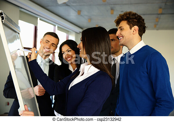 Happy business team with flip board in office - csp23132942