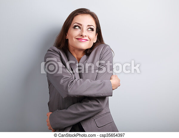 Happy business woman hugging herself with natural emotional enjoying face and thinking look. Love concept of yourself.  - csp35654397