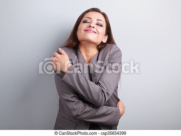 Happy business woman hugging herself with natural emotional enjoying face. Love concept of yourself - csp35654399