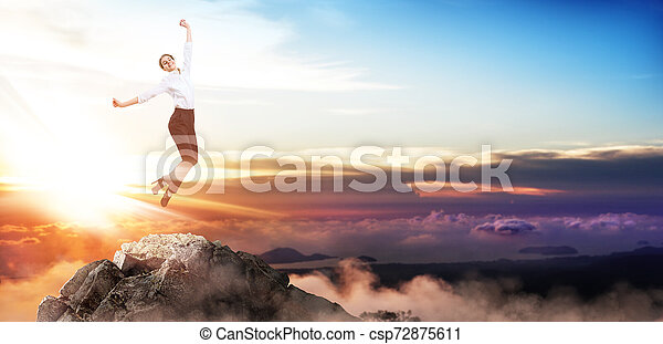 Happy business woman jumps up on mountain peak. - csp72875611