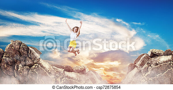 Happy business woman jumps up on the gap. - csp72875854