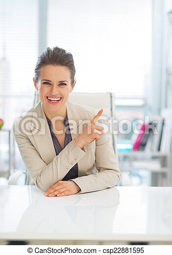 Happy business woman pointing on copy space - csp22881595