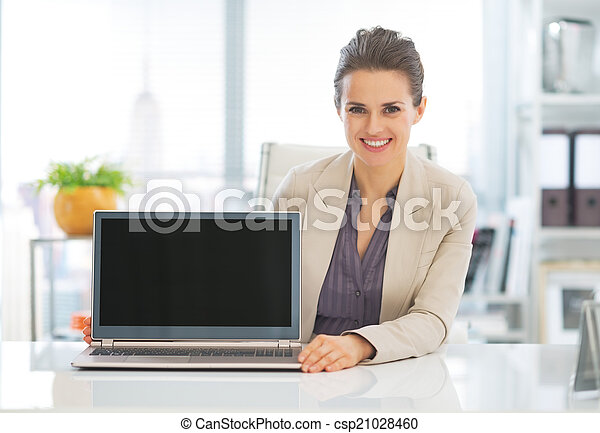 Happy business woman showing laptop blank screen - csp21028460