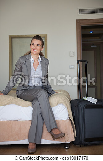 Happy business woman sitting on bed in hotel room - csp13017170