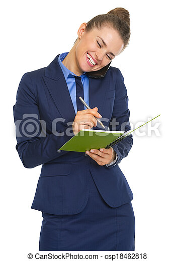 Happy business woman talking mobile phone and writing in notepad - csp18462818