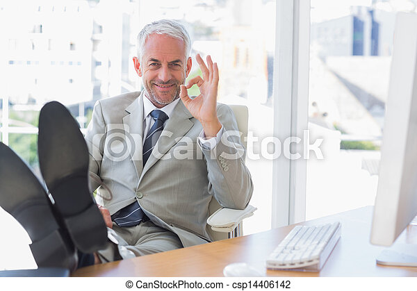 Happy businessman giving ok sign with feet up - csp14406142