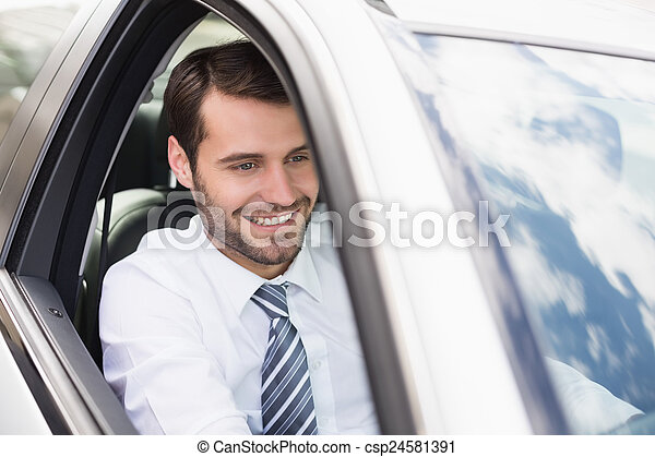 Happy businessman in the drivers seat - csp24581391