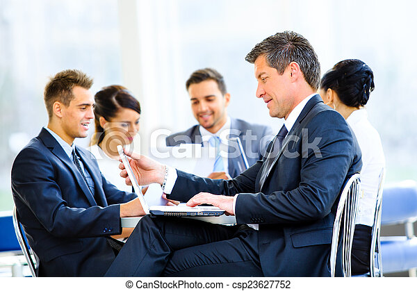 Happy businessman using laptop in business building, smiling. - csp23627752
