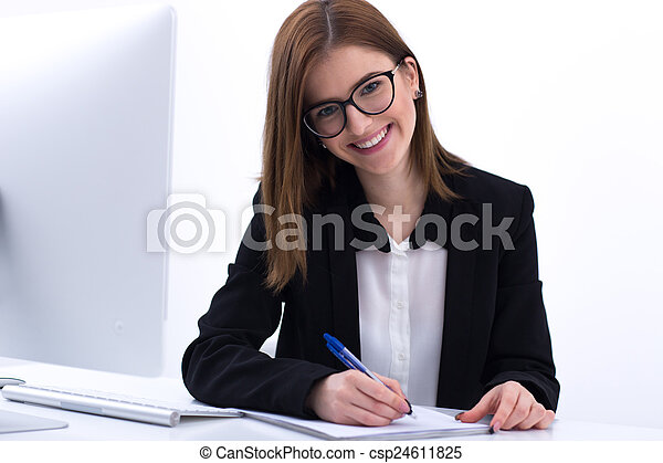 Happy businesswoman sitting at her worplace and writing something in notebook - csp24611825
