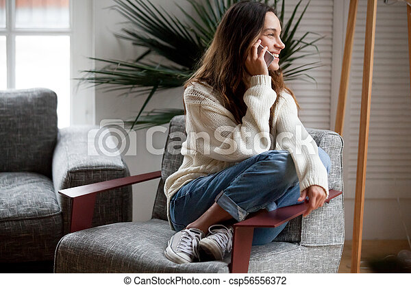 Happy cheerful young woman talking on the phone at home - csp56556372