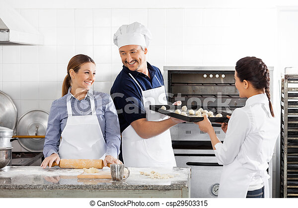 Happy Chefs Baking In Kitchen - csp29503315