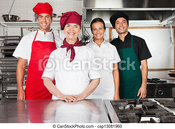 Happy Chefs Standing Together In Kitchen - csp13081960