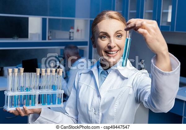 happy chemist in lab coat holding tubes at laboratory csp49447547