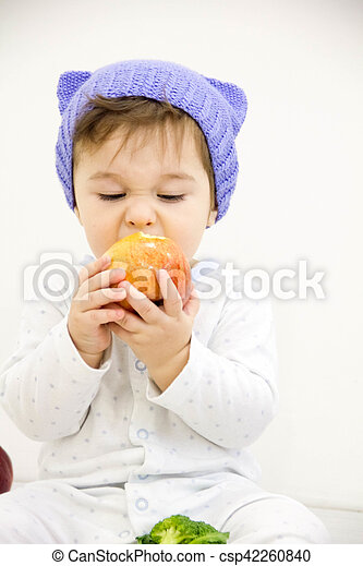 Happy child baby boy sitting in diaper and eating green apple blue eyes looking at the corner isolated on a white background - csp42260840
