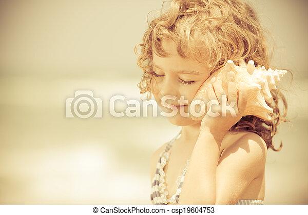 Happy child listen to seashell at the beach - csp19604753