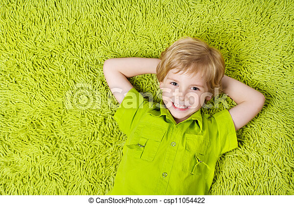Happy child lying on the green carpet background. Boy smiling and looking at camera - csp11054422